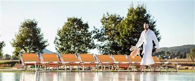 Mann in Bademantel vor Ruheliegen auf einer Grünfläche