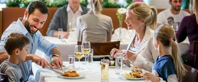 Familie sitzt an einem gedeckten Restauranttisch und isst zu Mittag