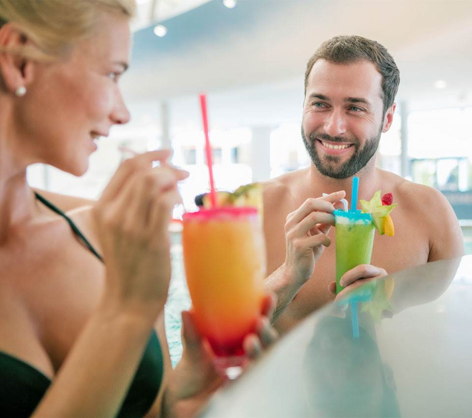 Couple drinks cocktails at a bar in a thermal resort
