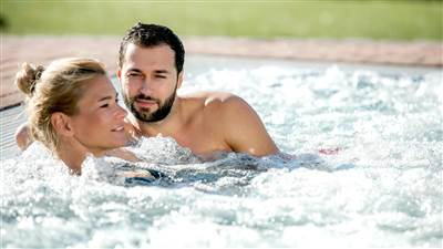 Couple relaxes in outdoor whirlpool
