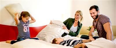 Familie mit zwei Kindern auf Hotelbett und macht Polsterschlacht
