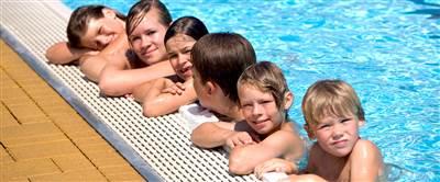 Kinder stehen im Wasser am Beckenrand im in einem Pool